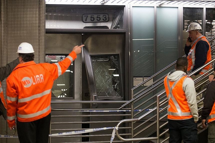 Officials inspecting the Long Island Rail Road train that derailed after striking a bumping block at Atlantic Terminal in Brooklyn on Wednesday. About 430 passengers and three crew members were on board at the time of the collision.