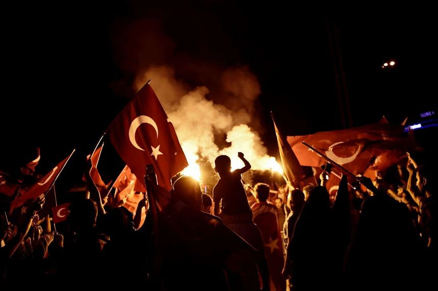 Pro-Erdogan supporters waving Turkish national flags during a rally at Taksim square in Istanbul on July 18, 2016, following the military failed coup attempt of July 15. Turkey has dismissed over 6,000 people under the state of emergency imposed afte