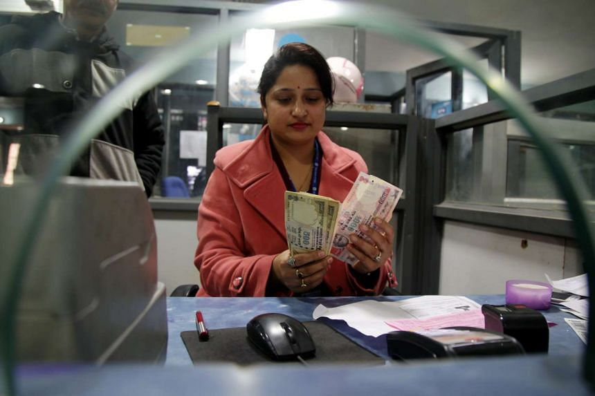 A bank clerk counting old Indian rupee notes at a bank in Kashmir, India. Economists have pared India's growth forecast to 6.3 per cent to 6.4 per cent for the 2016/17 fiscal year, citing the impact of the demonetisation.