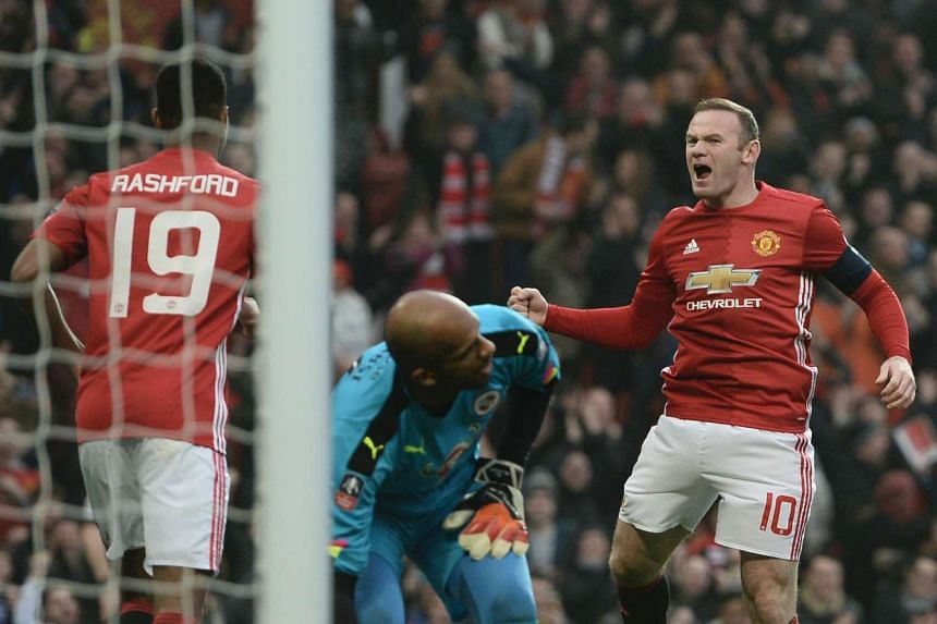 Manchester United's English striker Wayne Rooney (right) celebrates scoring the opening goal and equalling Bobby Charlton's Manchester United all-time scoring record during the English FA Cup third round football match in Manchester, north west Engla