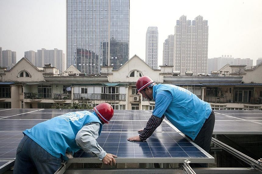 Workers installing solar panels on a rooftop in Wuhan, China, last month. This week, China's National Energy Administration announced that it will plough 2.5 trillion yuan (S$518 billion) into renewable power generation by 2020, as it moves from trad
