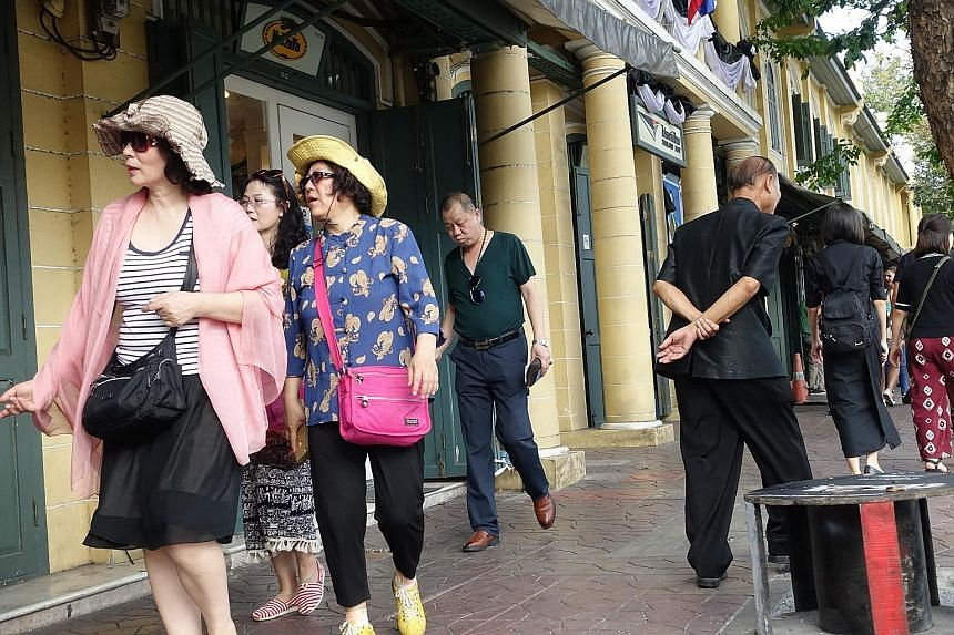 Left: The bright attire of Chinese tourists strikes a contrast against mourners on their way to Bangkok's Grand Palace to pay respects to the late king. Top: Singapore hotel chain Clover opened an outlet in Bangkok in March last year. Its occupancy r