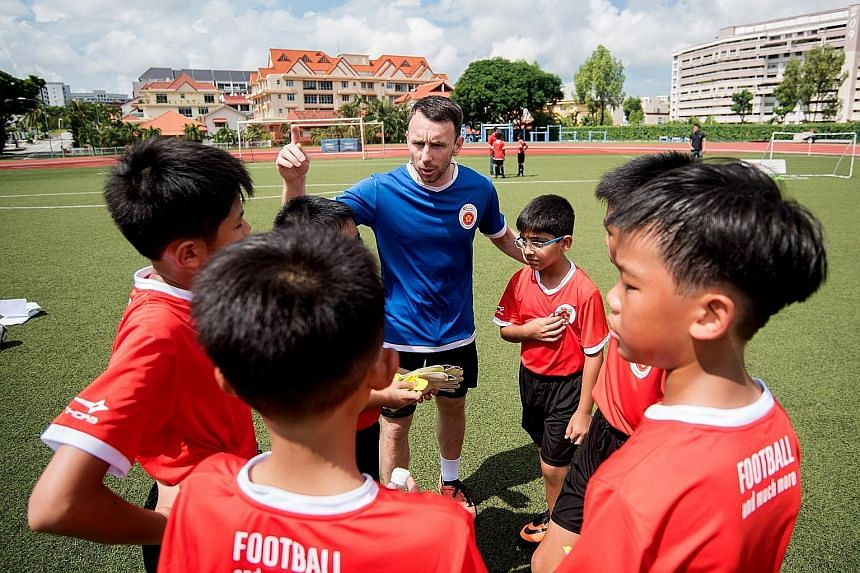 Volunteer assistant coach Kenneth McGeough briefing the participants of the ActiveSG football academy. SportSG will get more involved in football by holding the purse strings for the Football Association of Singapore.