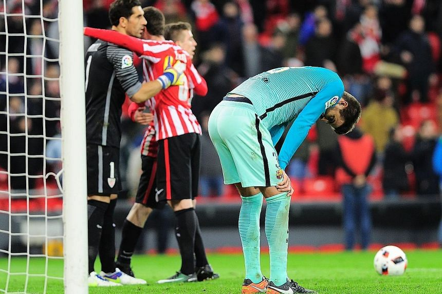 Barca defender Gerard Pique bends over in disappointment, as Bilbao celebrate their 2-1 win in the first leg of the Spanish King's Cup last-16 tie. They will hope to be sixth time lucky after never beating their rivals in their last five Cup meetings