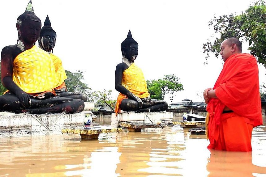 A Buddhist monk wades through flood waters at a temple in Surat Thani province. Nine provinces along Thailand's southern tail have been hit by unseasonable rain for nearly a week. People unloading the food supplies to be distributed to flood victims