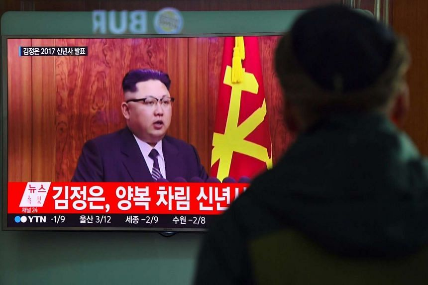 A man watches a television news broadcast at a railway station in Seoul, which shows North Korean leader Kim Jong Un's New Year's speech.
