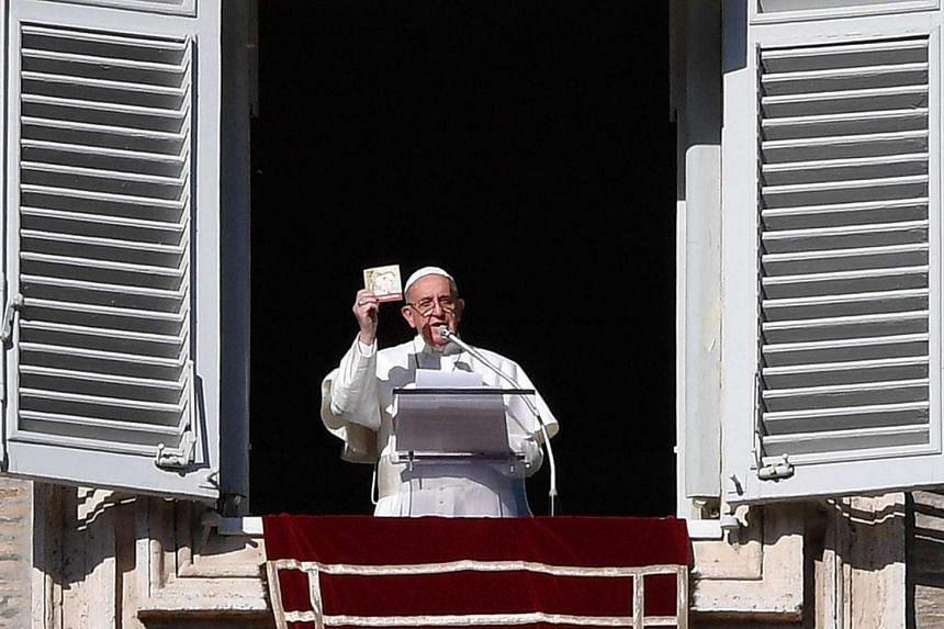 Pope Francis shows a booklet on Jesus Christ that will be distributed to faithful during the Angelus prayer, from a window of the Apostolic Palace at Saint Peter's Square, Vatican City on Jan 6, 2017.