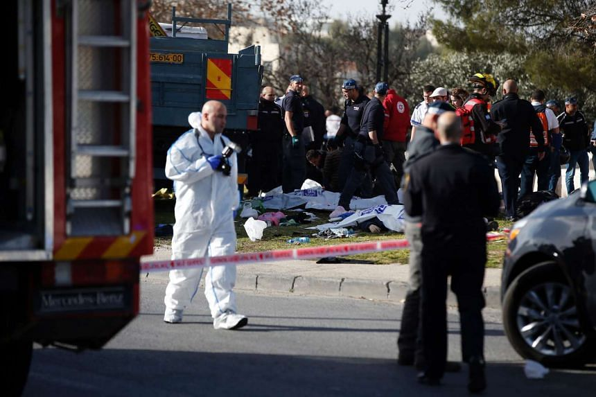Israeli security forces and medics gather around a flatbed truck at the site of a ramming attack in Jerusalem on Jan 8, 2017.