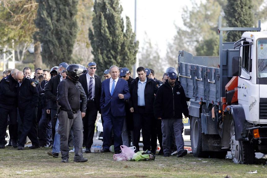 Israeli Prime Minister Benjamin Netanyahu (centre) visits the site of a vehicle-ramming attack in Jerusalem on Jan 8, 2017.