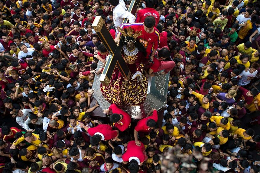 Devotees watch as a replica of the Black Nazarene is carried along a road during a procession in Manila on Jan 7, 2017.