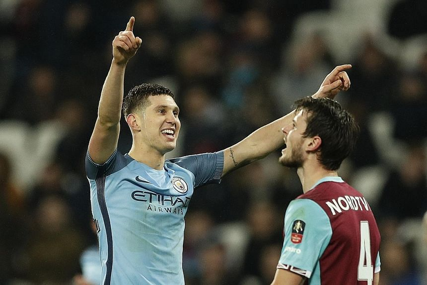 Manchester City defender John Stones celebrating after scoring their fifth goal against West Ham on Friday. City won the FA Cup third-round tie 5-0.