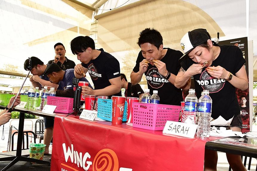 Mr Zermatt Neo and Ms Sarah Ow emerged winner and runner-up respectively at the inaugural Food League Singapore eating contest yesterday. Ms Ow finished 88 chicken wings in the same time Mr Neo polished off his 92.