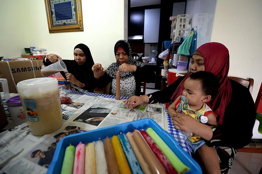 MADAM SALBIAH AHMAD, flanked by her daughter, Ms Siti Fatimah Musa (right), and daughter-in-law, Ms Suliama Sulaiman, making ice lollies. Ms Siti is holding her son, 18-month-old Harith Danial.