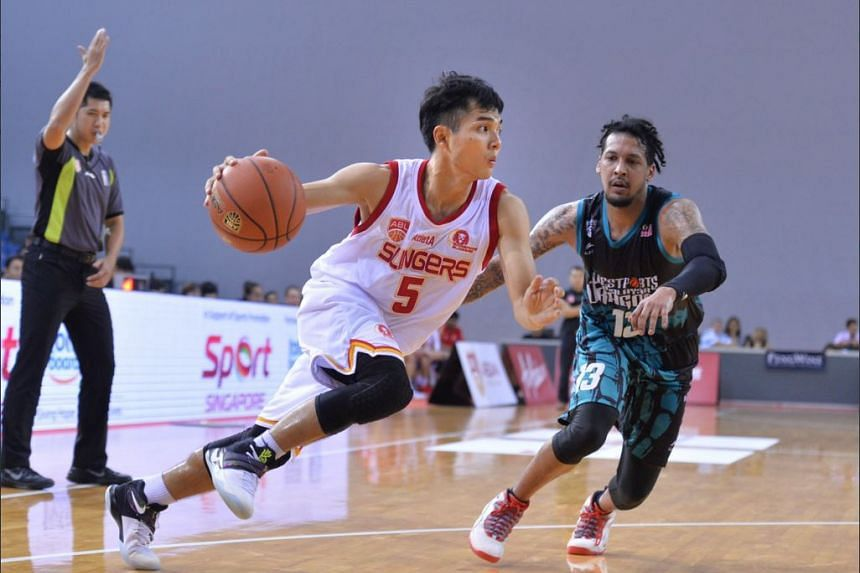 Singapore Slingers guard Wong Wei Long (#5) driving against Westsports Malaysia Dragons Frederick Lee (#13) during their match at the OCBC Arena on Jan 8, 2017.