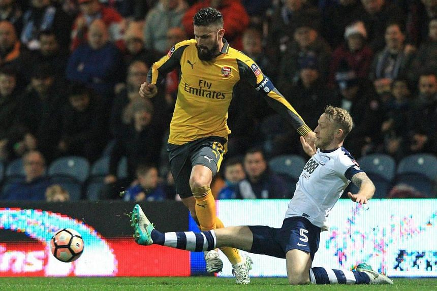 Arsenal's French striker Olivier Giroud (left) vies with Preston's English defender Tom Clarke during the English FA Cup third round football match between Preston North End and Arsenal on Jan 7, 2017.