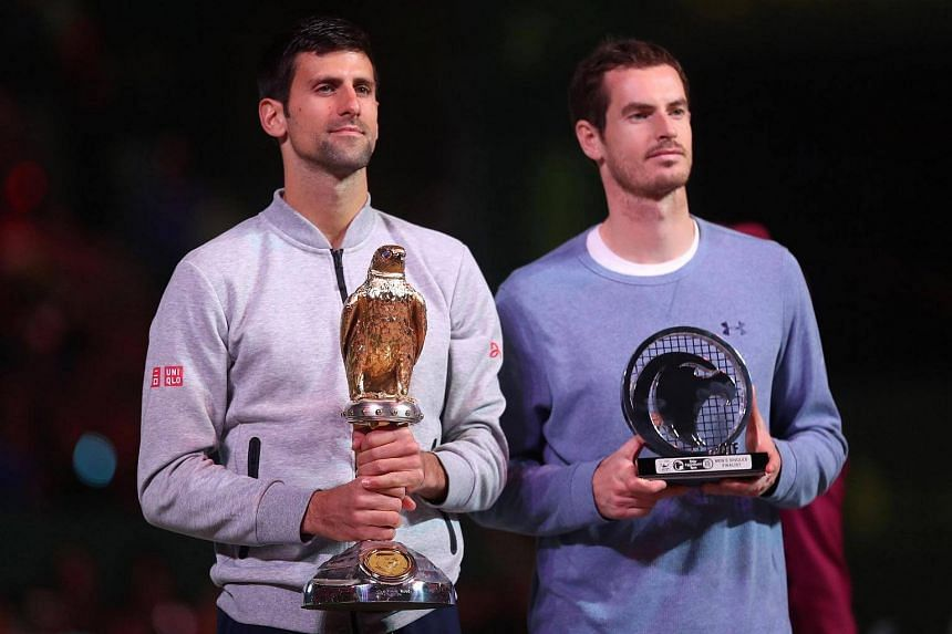 Serbia's Novak Djokovic (left) poses with the winner's trophy after beating Britain's Andy Murray during their final tennis match at the ATP Qatar Open in Doha on Jan 7, 2017.