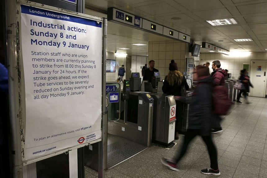 Passengers passing through ticket turnstiles in Waterloo Station next to a notice giving details of a strike by London Underground workers, on Jan 9, 2017.