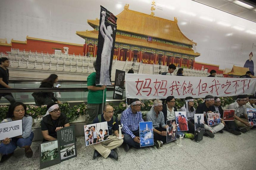Pro-democracy protestors gather in front of a banner advertising the Palace Museum project at the Central MTR subway station in Hong Kong, China on Jan 9, 2017.