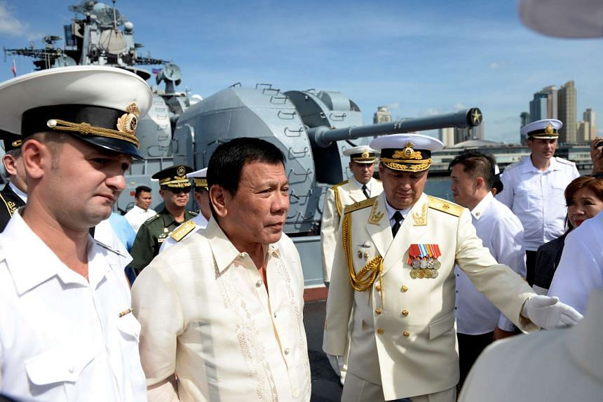 Russia's Rear Admiral Eduard Mikhailov (right) leads the way as he guides Philippine President Rodrigo Duterte (second from left) at the anti-submarine navy ship Admiral Tributs at the south pier in Manila on Jan 6, 2017.