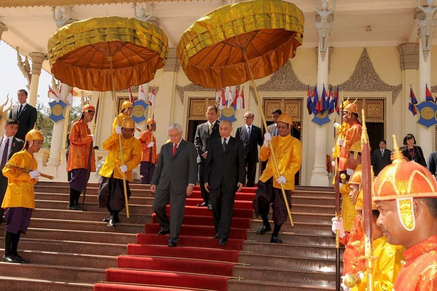Singapore's President Tony Tan Keng Yam (centre-left) and Cambodian King Norodom Sihamoni walk down the stair after a meeting at the Royal Palace in Phnom Penh on Jan 9, 2017.