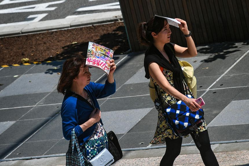 Women shelter themselves with magazines outside National Gallery Singapore on a blistering hot day on Jan 7, 2017.