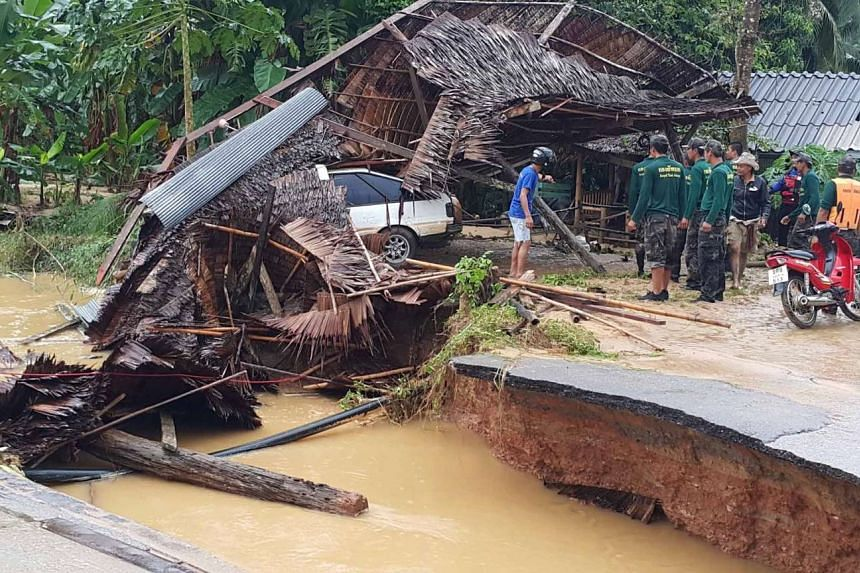 People inspecting the damage of a collapsed road due to heavy flooding in the Langsuan district of the southern Thai province of Chumpon, on Jan 7, 2017.
