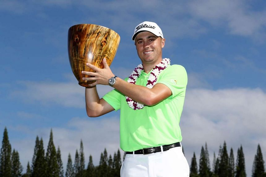 Justin Thomas of the United States celebrating with the trophy on the 18th green after winning during the final round of the SBS Tournament of Champions at the Plantation Course at Kapalua Golf Club on Jan 8, 2017 in Lahaina, Hawaii.