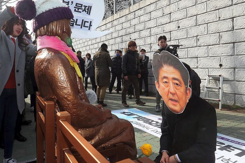 """A South Korean protester donning a mask of Japanese Prime Minister Shinzo Abe, in a mock apology in front of a """"comfort woman"""" statue, outside the Japanese consulate in Busan last week."""