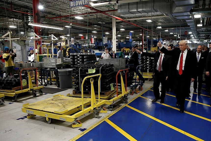 Mr Trump visiting a factory in Indiana on Dec 1. His campaign maintained that manufacturing jobs were lost overseas, but experts say automation is another factor and new plants are unlikely to bring jobs back.
