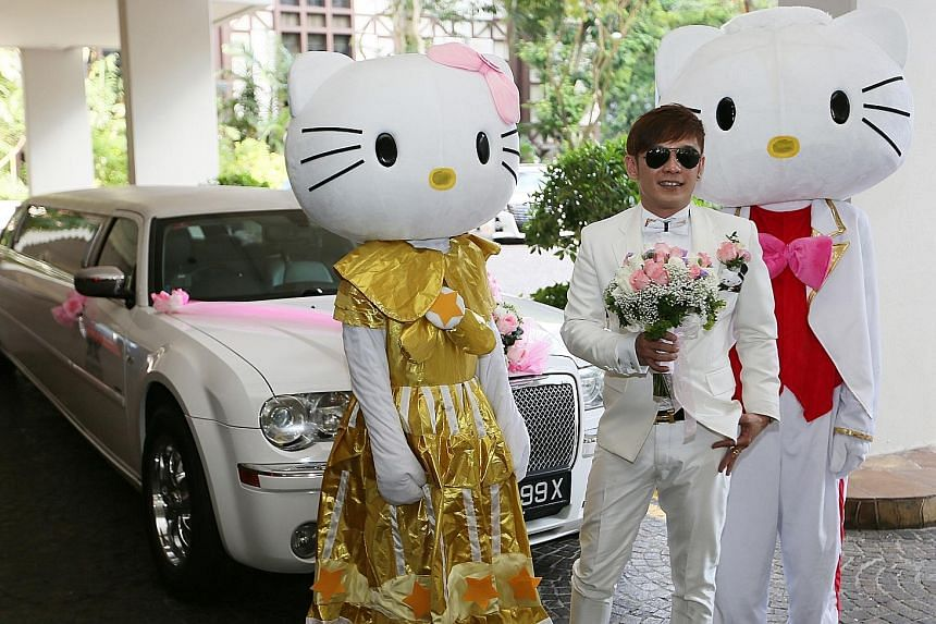 Two personalities from the getai show business got hitched last Saturday with a procession of 11 luxury cars, two Hello Kitty mascots (above).