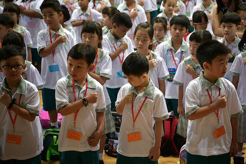 Westwood Primary 1 pupils figuring out how to place their fist on their chest before reciting Singapore's National Pledge during morning assembly last Tuesday.