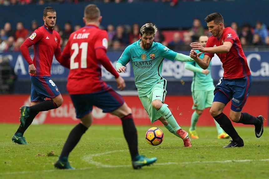 Barcelona's Argentinian forward Lionel Messi (centre) vying with Osasuna's defender David Garcia during the Spanish league football match CA Osasuna and FC Barcelona on Dec 10, 2016.
