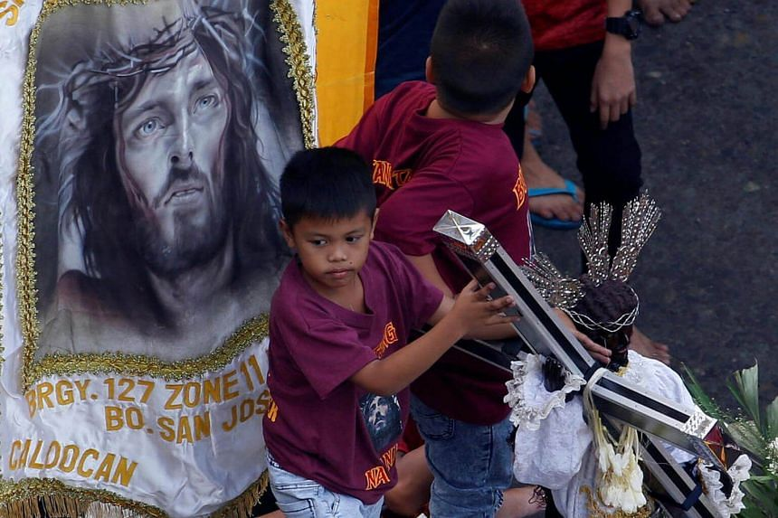 A boy holding on to a replica of the Black Nazarene as they wait for the main religious procession in Manila, Philippines, on Jan 9, 2017.