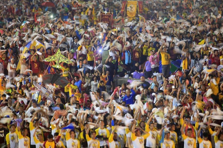 Devotees waving handkerchiefs as they sing a religious hymn before the start of the annual procession of the Black Nazarene in Rizal park, metro Manila, Philippines, on Jan 9, 2017.