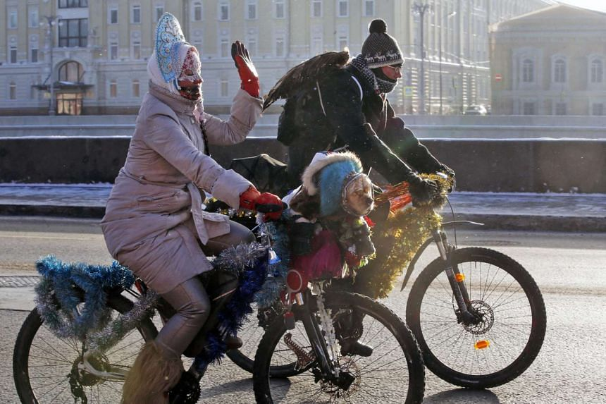 Wrapped in warm clothes a cyclist has her pet dog accompanying her during a winter bike parade in Moscow on Sunday (Jan 8, 2017).