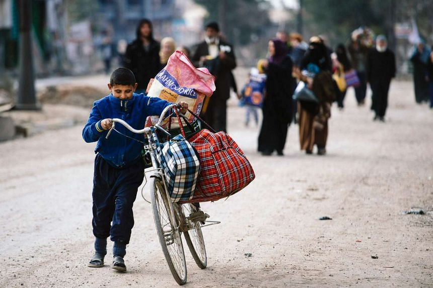 An Iraqi boy pushes a bicycle in Mosul's al-Zahraa neighbourhood on Jan 8, 2017, as he flees with others during an ongoing military operation against ISIS,