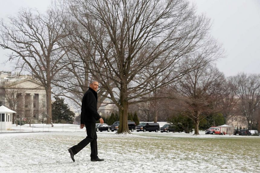 US President Barack Obama walks through the snow to Marine One as he departs the White House in Washington on Saturday (Jan 7, 2017).