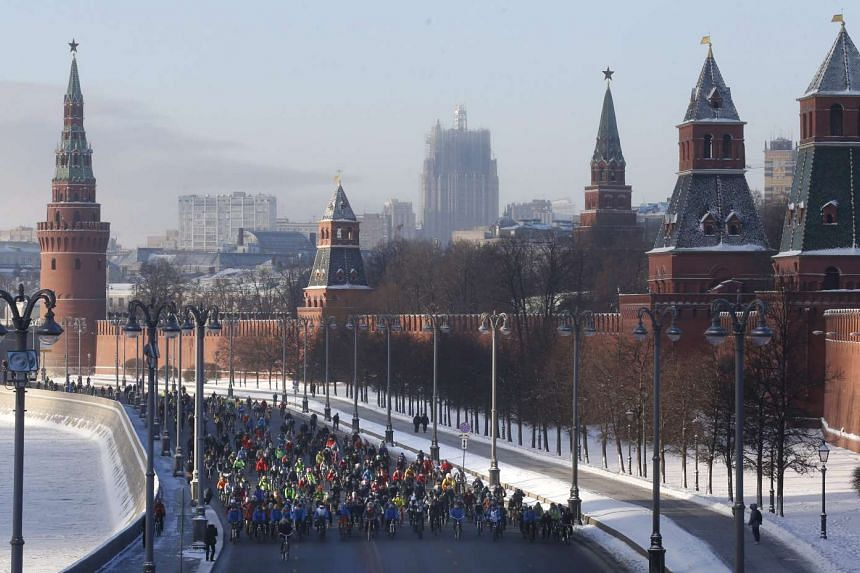 Cyclists pass by the Kremlin as they take part in a winter bike parade in Moscow on Sunday (Jan 8, 2017).
