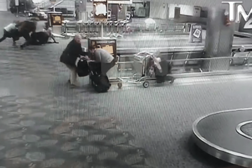 One woman hid behind a luggage cart as others ducked for cover following a brief moment of stunned confusion.