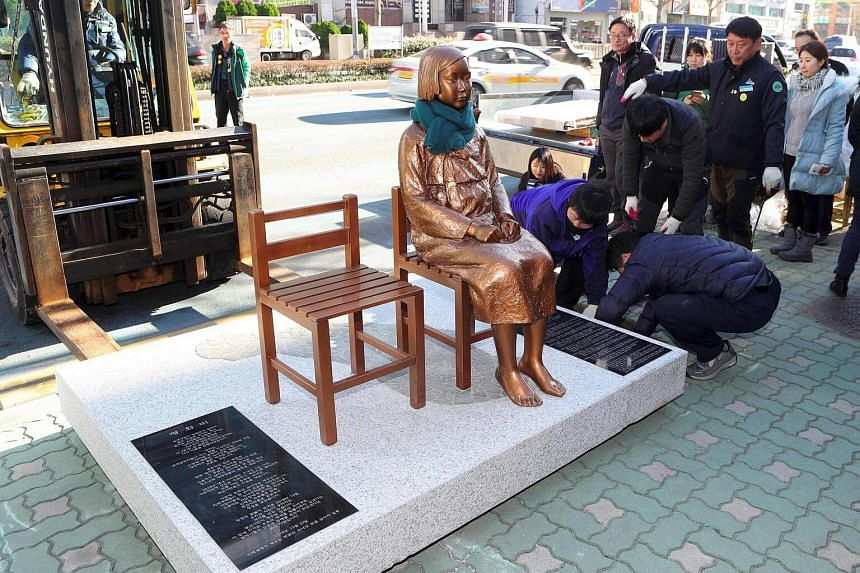 """Workers setting up a statue of a teenage girl (centre) symbolising """"comfort women"""" who served as sex slaves for Japanese soldiers during World War II, outside the Japanese consulate in Busan, on Dec 30, 2016."""