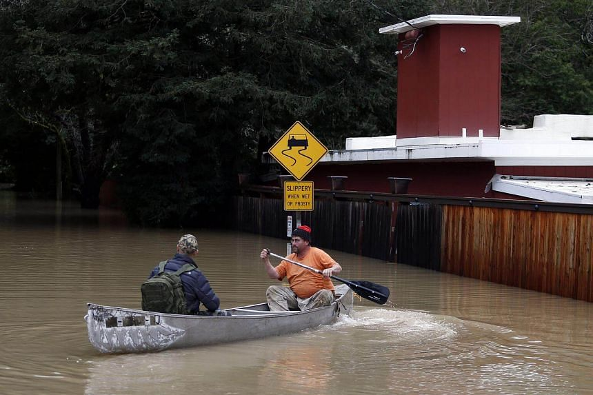 A resident kayaking on a road flooded due to the rising levels of the Russian River in Guerneville California, US, on Jan 9, 2017.