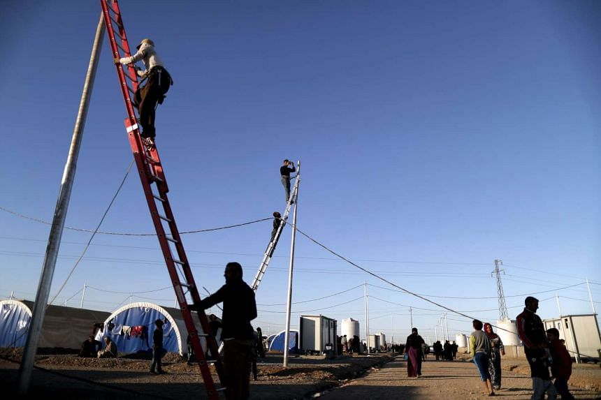 Workers install electric wires for Iraqi refugees as they set up a new part of the Khazir refugee camp near the Kurdish checkpoint of Aski Kalak, 40km West of Arbil, the capital of the autonomous Kurdish region of northern Iraq, on Nov 21, 2016.