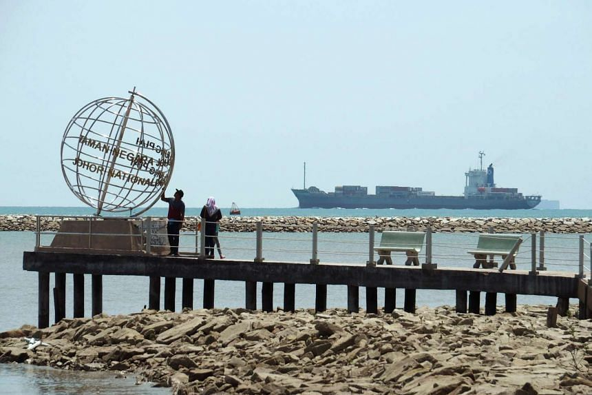 A container ship entering the Singapore Strait for the Strait of Malacca, as tourists stand at mainland Asia's southern most point in Johor, Malaysia, on Nov 12, 2016.