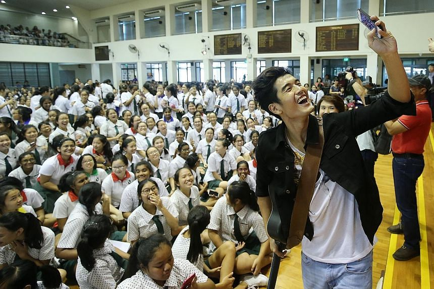 Hartono taking a photo with students of St Margaret's Secondary School, where he gave an assembly performance to promote the learning of the Chinese language.