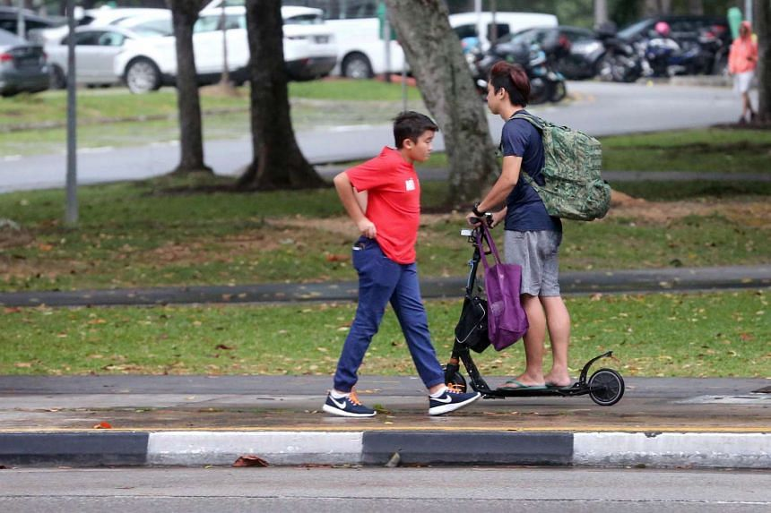 A pedestrian walking past a man travelling on e-scooter on the pavement on Sept 21, 2016.