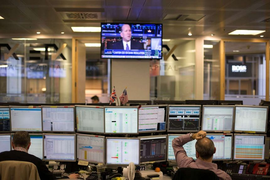 Traders sit in front of trading screens at ETX Capital in central London in January, 2017.