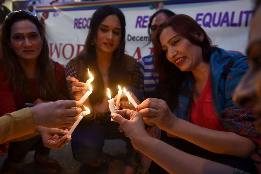 Pakistani transgenders light candles during a rally on World AIDS Day in Karachi on Dec 1, 2016.