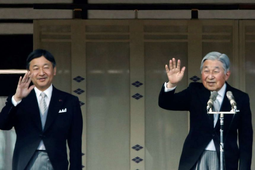 Japanese Emperor Akihito (right) and Crown Prince Naruhito wave to well-wishers during a public appearance for New Year celebrations at the Imperial Palace in Tokyo, Japan on Jan 2, 2017.