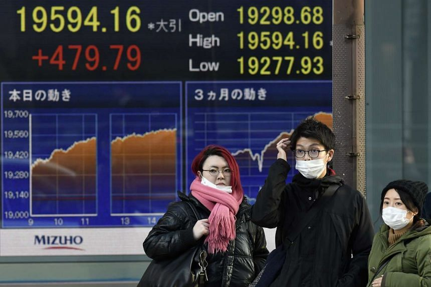 Pedestrians stand in front of a stock markets indicator board in Tokyo, Japan on Jan 4, 2017.