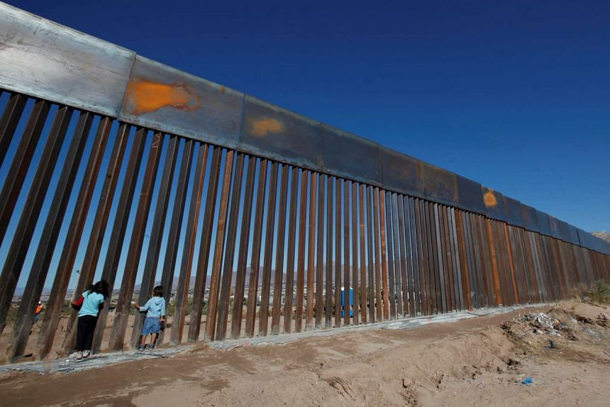 Children play at a newly built section of the US-Mexico border wall at Sunland Park, U.S. opposite the Mexican border city of Ciudad Juarez, Mexico on Nov 18, 2016.